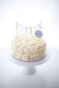 バラの花束のようなクリームのデコレーションが施されたケーキ。上に乗っているフラッグもキュートです。