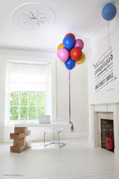 A minimal white work space supported by permanent rubber balloons tied with Carbo-Titanium ribbons and giant Jenga blocks