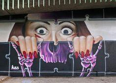 Sr. Kas artista de la calle de Portugal mural.  Cara de la mujer detrás de la pared