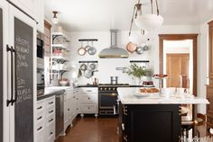 hanging pots, open shelves, marble counter extends for seating.