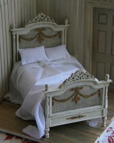 This is a miniature doll bed. I would like to do this to the caned headboard on the Master Bedroom bed, using carved swags and an Over Door or Cartusche, and perhaps gild some of it. My Petit Parterre