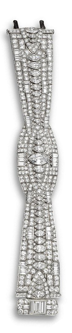 DIAMOND BRACELET, CIRCA 1930.  The central oval motif flanked by flared straps, set with a marquise-shaped diamond weighing approximately 1.90 carats and 34 marquise-shaped, 222 round and 44  bullet-shaped and baguette diamonds weighing a total of approximately 29.50 carats, mounted in platinum, length 7¼ inches.