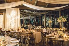 Wedding reception decor with white fabric draping, silver linens, wooden X-back chairs and white florals in silver and natural wooden vessels. Florals by Uncut Flowers, LLC, image by Vue Photography at The Farm at Old Edwards Inn and Spa in Highlands, NC.
