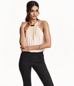 Flared halterneck top in crinkled, woven fabric. Rigid metal necklace at neckline decorated with narrow chains. Concealed zip at back. Lined.