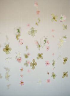 make your own flower mobile by stringing fabric flowers on fishing line. you can buy the flowers at scrap booking stores.
