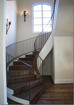 Across the center hall from the dining room is the stairwell. Simple—with iron sconces on the walls.
