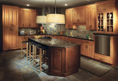 large kitchen has semi custom maple cabinets in a Shaker style, wide windows over sink looking out on fall colors, double wall oven, green subway tile backsplash, black granite countertop, mission corbels on island by leather bar chairs