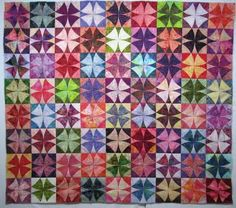 """A scrap quilt -- the one-block pattern is """"Winding Ways.""""  So a """"scrap"""" quilt just means that it's made up of many different fabrics, usually made in order to use up a quilter's remnants of fabrics that are left over from other projects."""