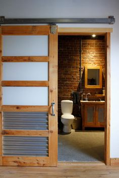Urban style bathroom. I love the sliding industrial door and how they used the original brick wall.
