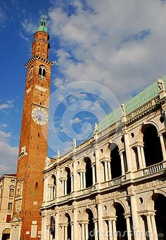Photo taken at the Palladian Basilica in Vicenza in Veneto Italy. In the image, taken from the Piazza dei Signori from the cathedral side, you see the facade that faces north sunlit of great historic and beautiful building in the city center. In addition to the white church we see the slender bell tower with clock that penetrates into the blue sky speckled with white clouds.