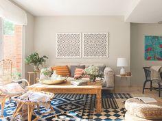En el salón, mesa auxiliar y butaca y reposapiés de ratán, en el estudio de la decoradora.