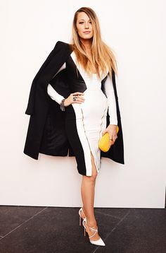 Blake Lively in a black and white dress with zips and black coat draped over the shoulders