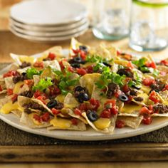 Nacho recipe with toppings of ground beef, lettuce, olives and zesty tomatoes for the ultimate snack.    Velveeta® is a registered trademark of Kraft Foods, Inc.   Ro*Tel® is a registered trademark of ConAgra Foods RDM, Inc.