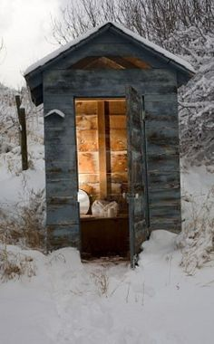 Out house in the backcountry that is covered in snow and ice
