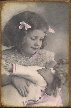Antique photo of little girl with doll.