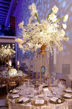 A winter wedding reception at the Art Institute of Chicago featuring icy blue uplighting, gold table setting details, & centerpieces overflowing with white calla lilies and Hawaiian orchids. #WeddingDecor Photography: Bob & Dawn Davis Photography. Read More: https://www.insideweddings.com/weddings/a-dream-winter-wedding-at-the-art-institute-of-chicago/563/