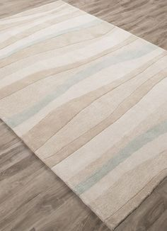 An seaside motif of the myriad shades of cream and sea blue found in shore sand dunes, will bring a calming sense to your seaside home with this hand-tufted, polyester rug.