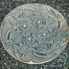 """An ornate manhole cover featuring salmon and a mask in downtown Vancouver"" Instagram @pinawa."