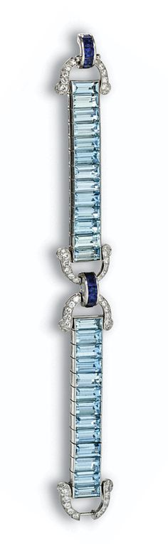 AQUAMARINE, SAPPHIRE AND DIAMOND BRACELET, CARTIER, CIRCA 1935.  Designed as two segments of channel-set rectangular aquamarines with stirrup-link terminals pavé-set with round and single-cut diamonds weighing approximately 2.75 carats, the center and clasp decorated with arched links of calibré-cut sapphires, mounted in platinum, length 7 inches, signed Cartier.