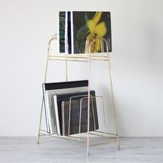 + mid century cart holder +    clean line metal stand with brass tone. formerly used for record storage, this piece has been repurposed as a magazine rack and book holder!