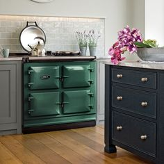 We're thrilled to re-introduce British Racing Green from our archive.  British Racing Green takes its name from the shade representing the UK within international motor racing.   There have been a number of green shades in the AGA palette since 1956, when colours other than the original cream were first introduced. These have ranged from the palest of hues right through to the darker end of the spectrum.  Now, AGA is bringing back its much-loved British Racing Green Barn Kitchen, Aga Kitchen, Green Interiors, Cast Iron Oven, Aga, Green Kitchen Cabinets, Country Kitchen Inspiration, Victorian Kitchen, Home Decor