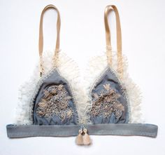 The bra is made by a grey ellastic-tulle with an ecru coloured lace. The flowers are hand embroidered. There is an inner lining which is made by