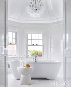 In the master bath, an Apparatus Cloud chandelier hangs above an Elizabeth Dow side table. The tub fixtures are from Waterworks.