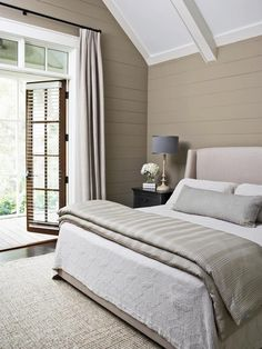 Neutral Bedroom With French Door - Minimizing color distraction on the walls, floors and furnishings is one of the ways that Linda McDougald, lead designer at the South Carolina-based firm Postcard from Paris, made this tiny bedroom feel bigger. The other major visual trick she employed was to add horizontal wood planking to the walls