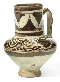 A FINE AND INTACT KASHAN LUSTRE POTTERY JUG   CENTRAL IRAN, 12TH/13TH CENTURY   On short flaring foot, with rounded body and tall straight neck, the painted decoration with stylized arabesques, the interior with cobalt blue glaze  4¼in. (11cm.) high