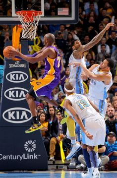 Kobe Bryant #24 of the Los Angeles Lakers goes to the basket against Corey Brewer #13, Wilson Chandler #21 and JaVale McGee #34 of the Denver Nuggets