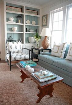 Painted bead board on the backs of bookcases- soft color with simple white display. Sofa against window. Rustic wood bench as cocktail table. Wood chair with soft graphic pattern