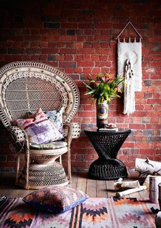 So much goodness happening here - peacock chair, weaving, rugs, pillows and flowers!