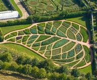 One of the twelve gardens located at La Chatonnière, in France, the Garden of Abundance is a vegetable garden shaped like a giant leaf. Each segment is filled with ornamental cabbages, strawberries, scallions, eggplant, basil, chives, parsley, tomatoes, celery, and red chard.