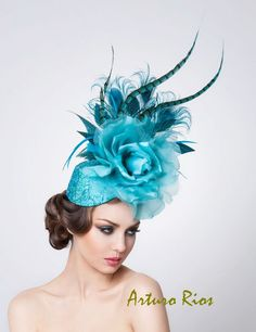Made on an oval base covered with Turquoise Silk and metalic Net with small Sequins.  Embelished with a Big silk Rose Assorted Peacock, Rooster, goose and Pheasant feathers. ArturoRios
