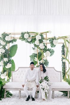 Stunning backdrop of white blooms and statement green leaves by Chenta Weddings at Puteh at Subang // Instead of focusing on the little details, Adham and Tati chose to focus on the things that make up a good wedding: family, friends, good food and the perfect [Spotify] dance tracks. The couple's Malaysia wedding solemnization and reception were held at Puteh at Subang and shot by The Jubsi Company; a tropical-inspired dais backdrop by Chenta Weddings and sparkly hanging piñatas amped