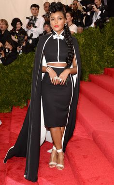 2015 Met Gala: Janelle Monae is wearing an H&M creation! The outfit include a black crop top, matching pencil skirt, and matching long cape. White is inside the cape and the edges of the whole outfit. I love this outfit on Janelle! I love her unique style. The top has Chinese inspiration which is the theme.