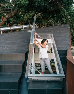 Kristine climbs out onto the concrete-tile roof deck through a hatch door in the upstairs loft.