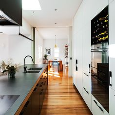 6mm porcelain benchtop with recycled timber frame, laminate cupboards and drawers, black detailed Hafele handles a bold rennovation in Brunswick #cosinteriors #modernkitchen #modernkitchendesign #kitchens #kitchendesigner #kitchen #kitcheninspo #laminate #blackhandles #blackfixtures #cabinetmakers #ecotimber #recycledtimber #brunswick