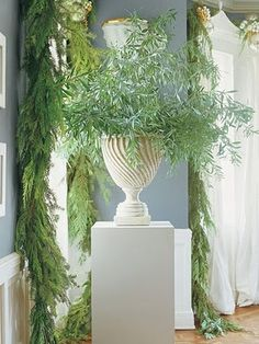 garlands surrounding windows and greenery in an urn on a plinth - Interior Designer, Mary McDonald - from Veranda Magazine - photographer Miguel Flores-Vianna