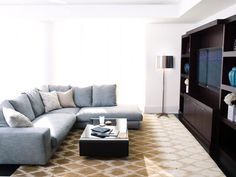 The centerpiece of this minimalist living room is a gray sectional sofa situated in front of a large wooden entertainment center. A metallic floor lamp adds a sleek touch, while a neutral diamond patterned area rug completes the look of the space.