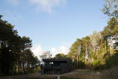 The blackened-timber facades of this house in a coastal nature reserve near The Hague are interrupted by carefully positioned openings that frame views of the surrounding forest.
