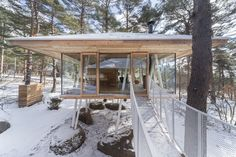 The stilts allow snow to gather underneath the structure, while walls of glass frame the surrounding winter wonderland.