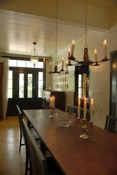 love the real candles in the chandelier, and the curtain flanking the front door. simple and warm.