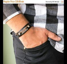 Un brazalete hermoso del abrigo para el hombre. Esta pulsera envuelve el cuero negro plano que envuelve 3 veces en su mano y un colgante plateado del infinito del doble de la plata.  Longitud:...