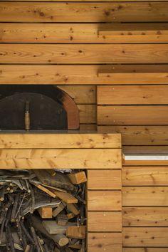 jardin en pente avec cuisine d'été, four à pin et espace de rangement bois