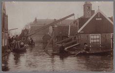 Straatbeeld tijdens de overstroming van Volendam. Op de achtergrond de R.K. kerk. Dorpsbewoners in schuitjes en twee ophaalbruggetjes. 1916 #NoordHolland #Volendam