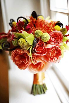 Colorful bouquet in peach, orange, yellow and green with billy balls, pin cushions, monkey's tail, cymbidium orchids, and roses