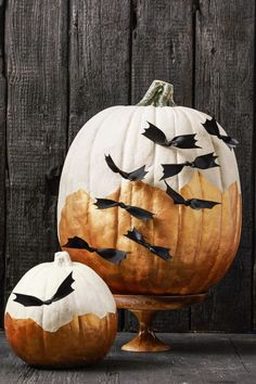 Don't worry about taping off neat lines for this gleaming design. A jagged horizon can set the stage for a spooky swarm of ribbon bats. Click through for the tutorial and more painted pumpkin decorating ideas for Halloween.