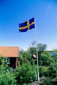 The Swedish flag and a red cottage by the water, Sweden. Johnér Bildbyrå AB Tel:+46 (0)8 6448330 - WS2