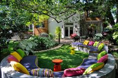 Curvy concrete garden seating with colorful cushions under an oak tree. Absolutely lovely.